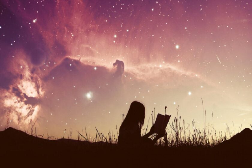 girl reading her dream journal under the stars